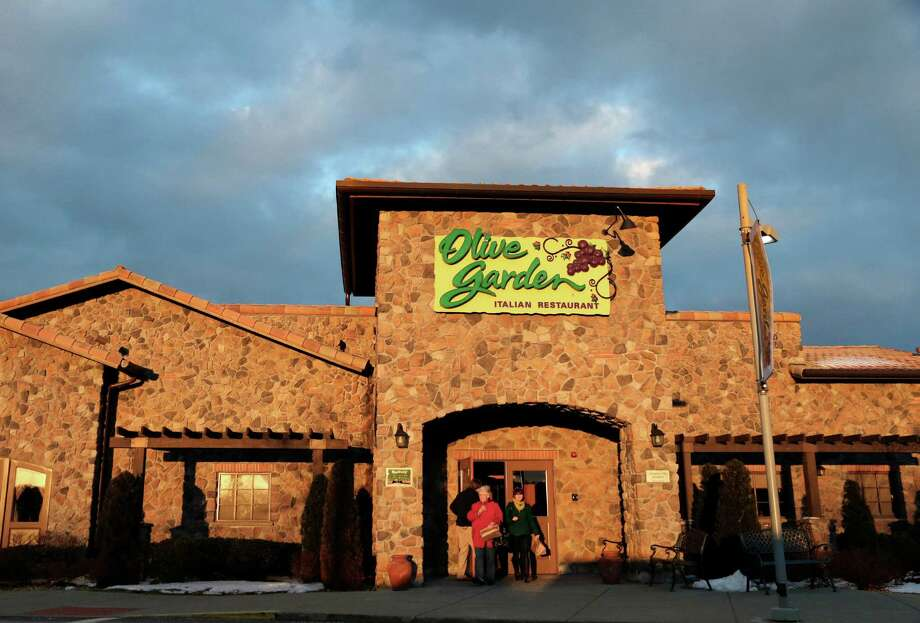 "In this Wednesday, March 20, 2013 photo people leave an Olive Garden restaurant at sunset in Foxborough, Mass. Darden Restaurants Inc., which has been struggling to hold onto customers in recent years, said Friday, June 21, 2013, that deal offers like a ""2 for $25"" dinner special helped drive up customer traffic at its flagship Olive Garden and Red Lobster chains in the latest quarter. The company said it will keep stressing the affordability of its food in the year ahead to attract more diners. Photo: Steven Senne"