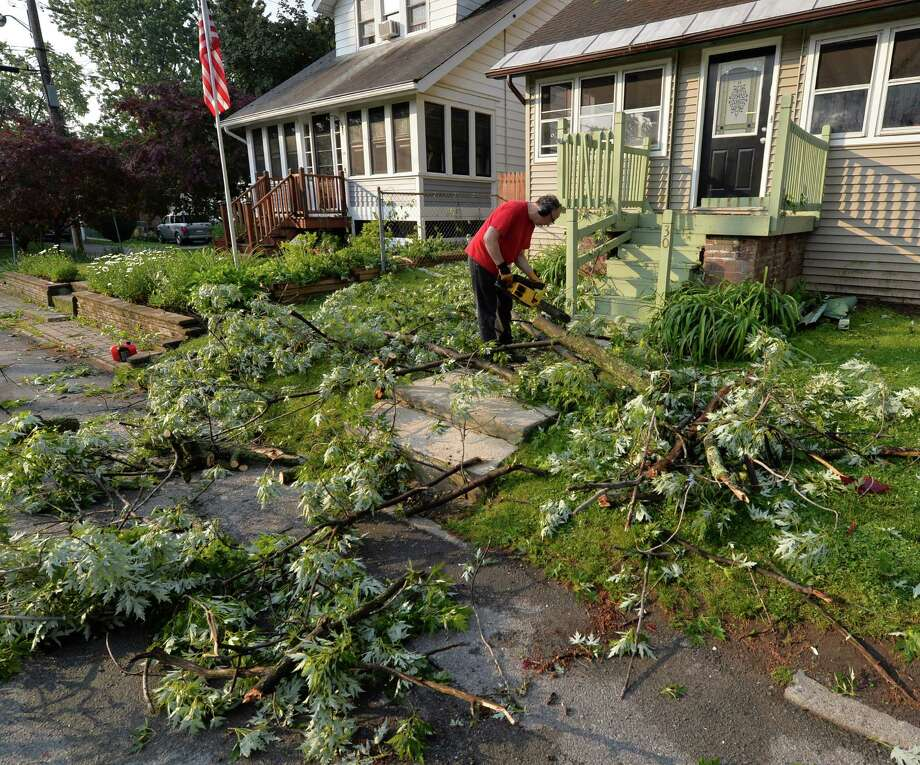 A good samaritan who asked that he not be identified removes branches from the front porch of 30 Ash Street June 25, 2013 after a severe storm hit Rensselaer N.Y. last evening.   (Skip Dickstein/Times Union) Photo: SKIP DICKSTEIN