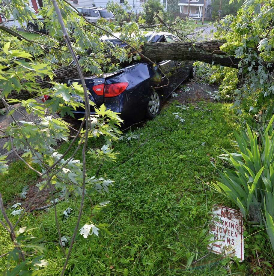 A Honda sedan lies under a tree on Ash Street June 25, 2013 after a severe storm hit Rensselaer N.Y. last evening.   (Skip Dickstein/Times Union) Photo: SKIP DICKSTEIN