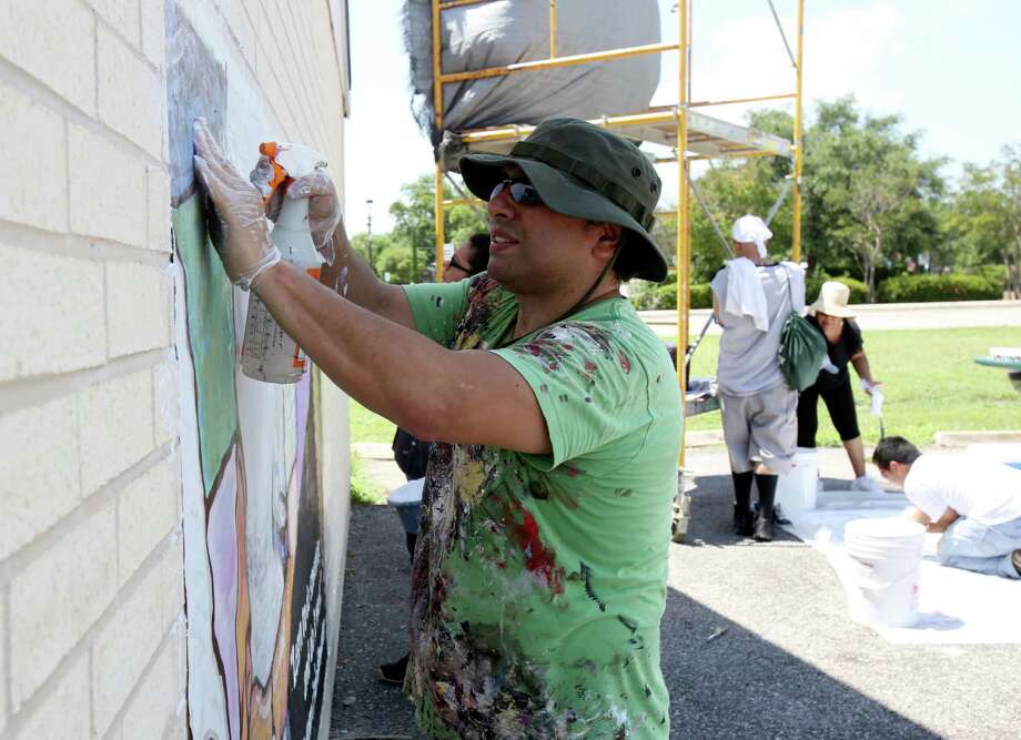 David Blancas installs a new mural on the St. Phillip's College Campus. Blancas has been the lead artist in a couple of murals on the West Side and hopes to spread spread murals to the east and west sides. Photo: Helen L. Montoya, San Antonio Express-News / ©2013 San Antonio Express-News