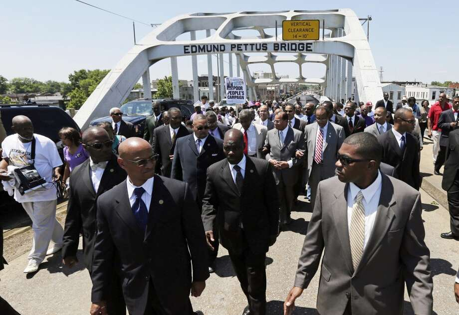 Nation of Islam Leader Louis Farrakhan (behind row of security with hands clasped) joins others in a march across the historic Edmund Pettus Bridge in Selma, Ala., on a voting rights caravan across Alabama on Friday, June 14, 2013. Farrakhan spoke at rallies earlier Friday in Birmingham and in Shelby County. (AP Photo/Dave Martin)