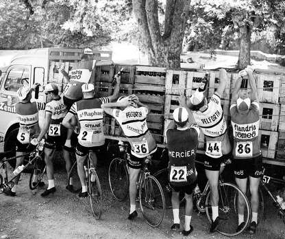 1964: Racing cyclists getting fresh supplies of wine in the during the 11th stage of the Tour de France between Toulon and Montpelier. Photo: Roger Viollet, Roger Viollet/Getty Images / Roger Viollet