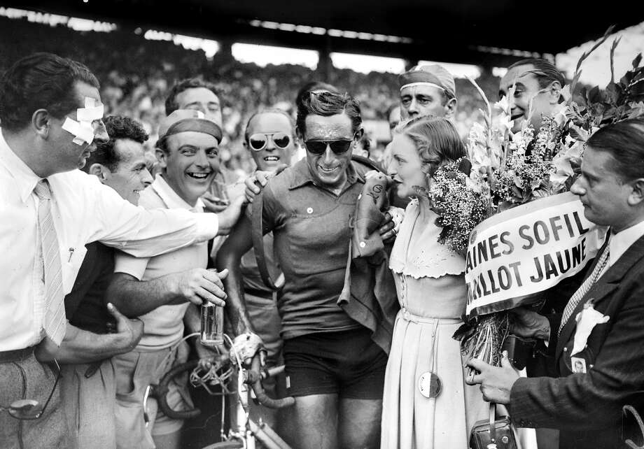 1949: Italian Fausto Coppi is congratulated upon his arrival at the Parc des princes in Paris, after winning the Tour de France. Photo: STAFF, AFP/Getty Images / 2013 AFP