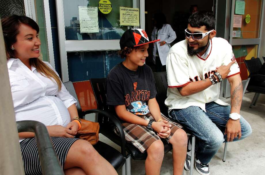 Sergio Romo talks with Sarah Lindberg and sixth grader, Laith Cuyjet, as they wait to receive vaccines at the Maxine Hall Health Center in San Francisco, Calif., on Tuesday August 14, 2012.  The San Francisco Immunization Coalition and San Francisco Department of Public Health were joined by the San Francisco Giants to remind parents and students that vaccines are required to attend school. Photo: Michael Macor, The Chronicle / ONLINE_YES