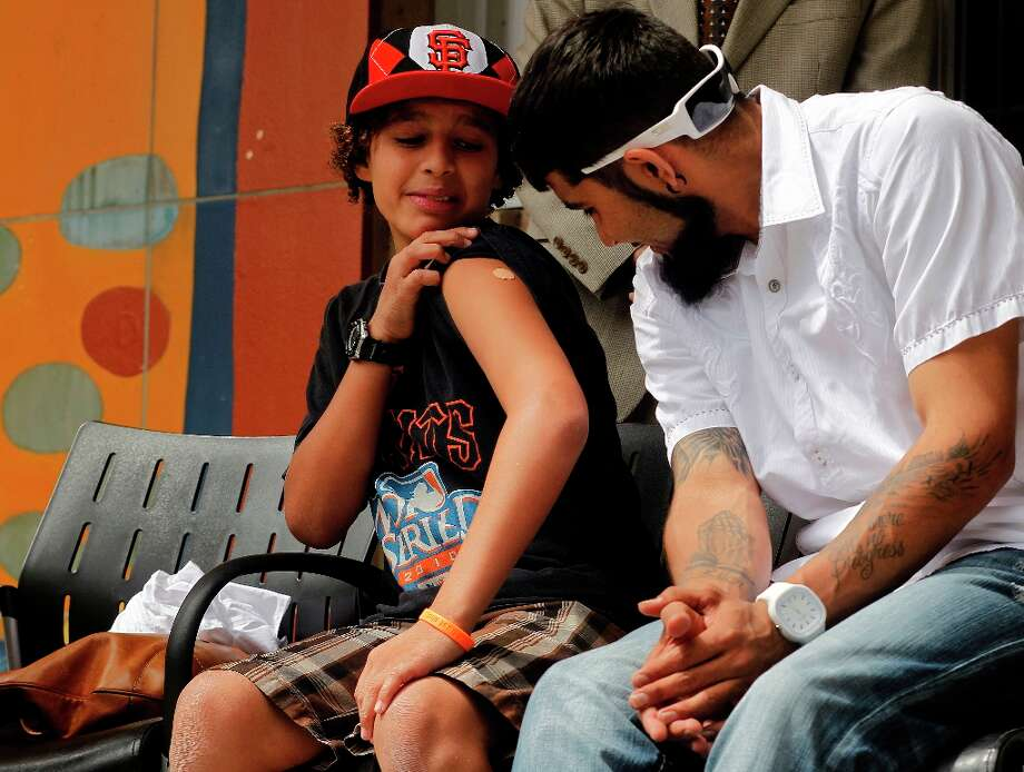 Sixth grader Laith Cuyjet shows off his vaccine to Sergio Romo. Photo: Michael Macor, The Chronicle / ONLINE_YES