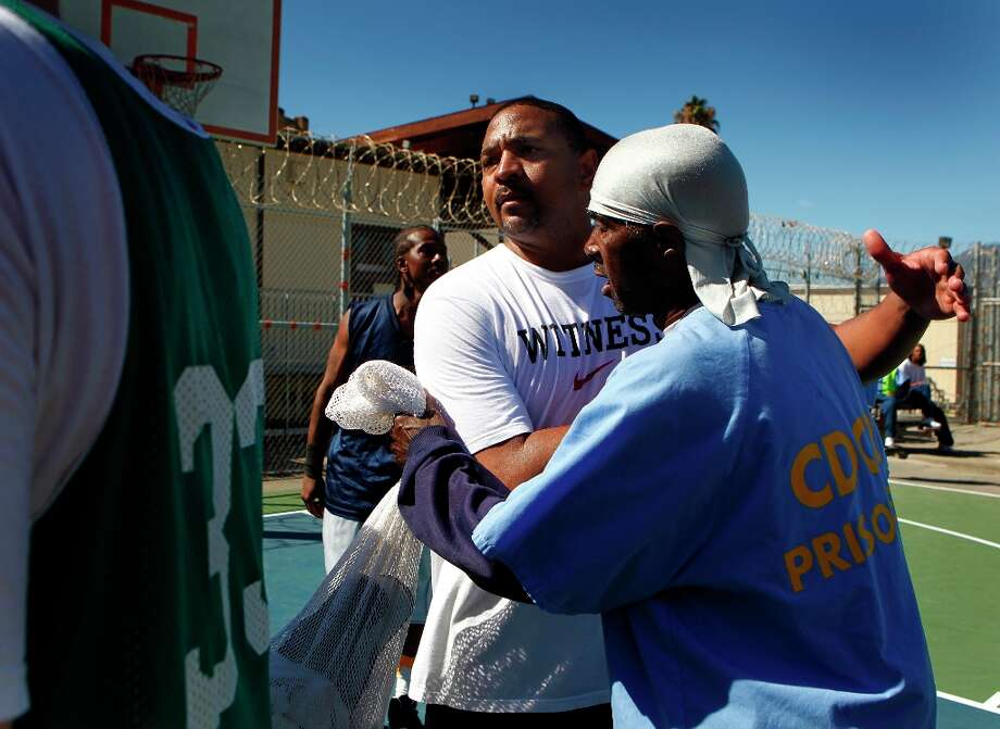 Golden State Warriors head coach Mark Jackson (center) hugs an inmate after a basketball game against the San Quentin Warriors at San Quentin State Prison on Saturday, Sept. 22, 2012. Photo: Paul Chinn, The Chronicle / ONLINE_YES