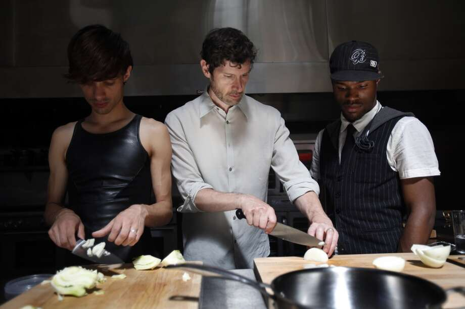 Chef Daniel Patterson, center, teaches Armand Seversson, left, and Ralph Willis, right, how to chop an onion.