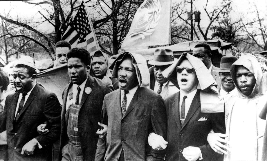 Rev. Dr. Martin Luther King, Jr. has his arms locked and singing as he leads a protest march to the racecourse in Montgomery. Photo: Popperfoto, Popperfoto/Getty Images / Popperfoto