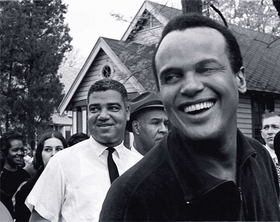 The actor and civil rights activist Harry Belafonte smiles broadly while marching with National Urban League director Whitney Young (1921 - 1971) and NAACP executive secretary Roy Wilkins (1901 - 1981), from Selma to the state capital of Montgomery, Alabama, March 1965. The actress Ina Balin is partly visible over Young's right shoulder. Photo: Robert Abbott Sengstacke, Getty Images / Archive Photos