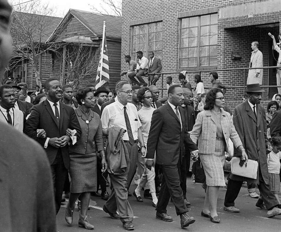 American Civil Rights leader Dr. Martin Luther King Jr. (1929 - 1968) and his wife Coretta Scott King (1927 - 2006) (center right, hand in hand) lead others during on the Selma to Montgomery marches held in support of voter rights, Alabama, late March, 1965. Among those with them are Reverend Ralph Abernathy (1926 - 1990) (second from left, smiling), and Pulitzer-Prize winning political scientist and diplomat Ralph Bunche (1904 - 1971) (front row, in white short sleeved shirt). Bunche's wife, Ruth (nee Harris, 1906 - 1988), holds Abernathy's arm. Photo: Robert Abbott Sengstacke, Getty Images / Archive Photos