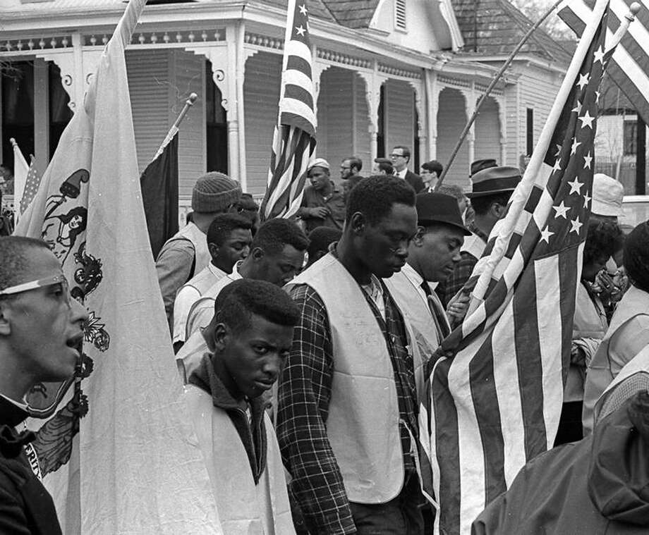 Marchers, carrying state and American flags, pause for a moment of silence during the Selma to Montgomery march held in support of voter rights. Photo: Robert Abbott Sengstacke, Getty Images / Archive Photos