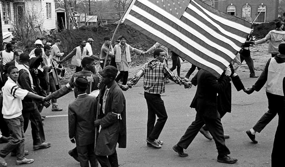 Marchers, hand in hand, walk past a fellow marcher waving an American flag, during the Selma to Montgomery march, held in support of voter rights in Alabama. Photo: Robert Abbott Sengstacke, Getty Images / Archive Photos
