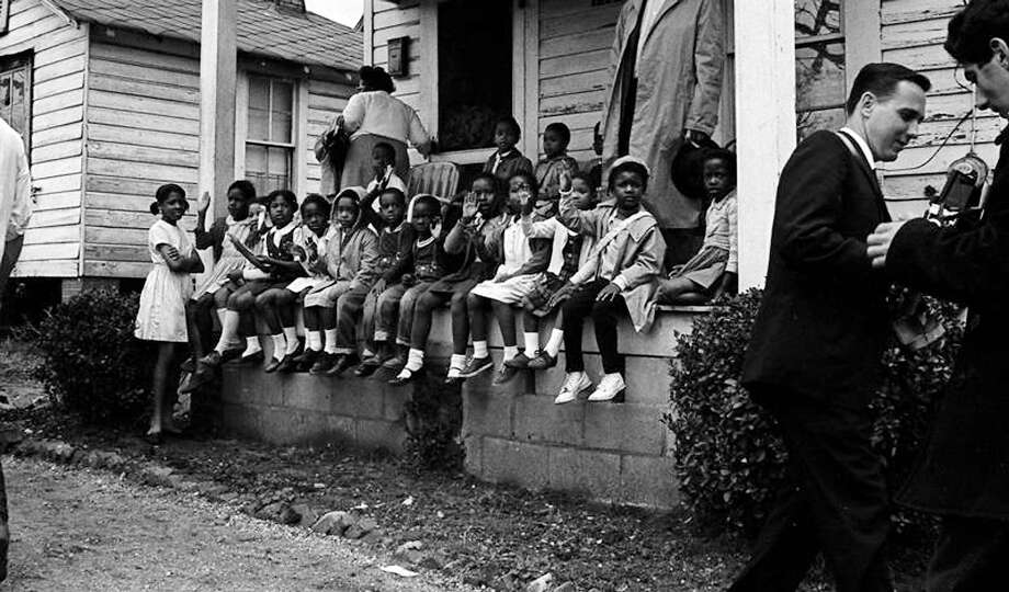Young children, sitting on their front porch, wave to marchers walking past their home, during the Selma to Montgomery marches held in support of voter rights. Photo: Robert Abbott Sengstacke, Getty Images / Archive Photos