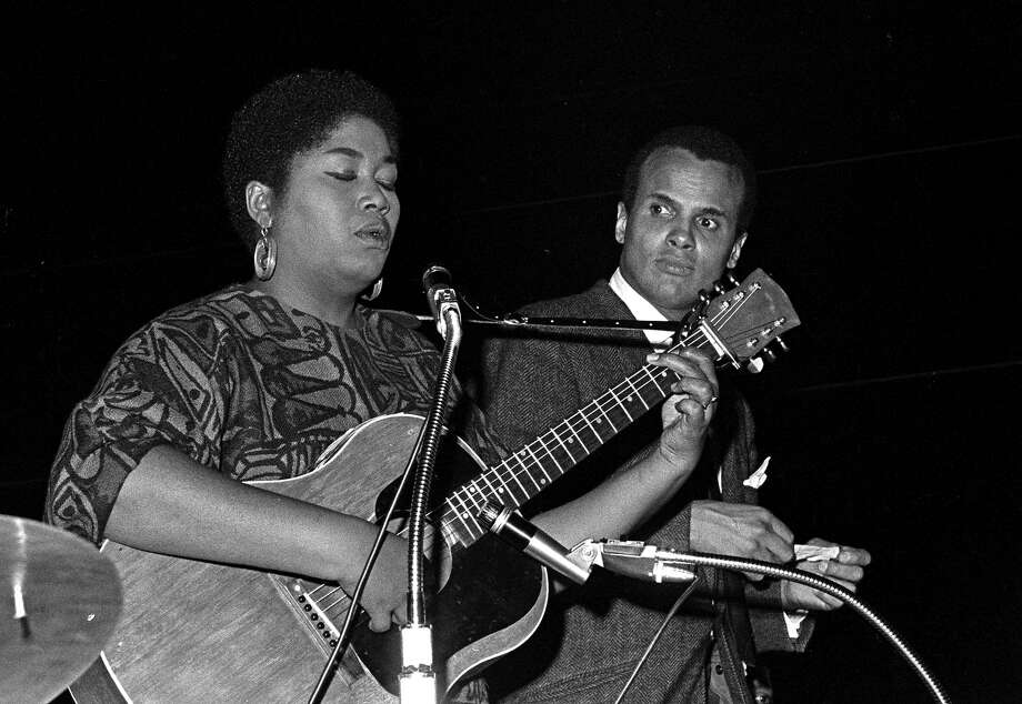 American singer and activist Harry Belafonte sings a duet with singer Odetta Holmes (1930 - 2008) at the 'Stars for Freedom' rally, Montgomery, Alabama, March 24, 1965. The rally occurred on the last night of the historic Selma to Montgomery march in support of voter rights; the following day, 25,000 marchers, led by American Civil Rights leader Dr. Martin Luther King Jr., arrived at the State Capitol Building and listened to King deliver his 'How Long, Not Long' speech. Singer and activist Harry Belafonte (left) stands behind him. Photo: Robert Abbott Sengstacke, Getty Images / ?? Robert A. Sengstascke 1988