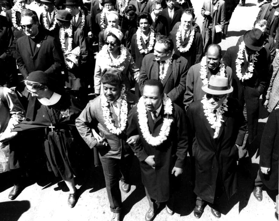 High-angle view of American Civil Rights leader Dr. Martin Luther King Jr. (1929 - 1968), flanked by Reverend Ralph Abernathy (1926 - 1990) and Pulitzer-Prize winning political scientist and diplomat Ralph Bunche (1904 - 1971) during the third Selma to Montgomery march for voting rights, Selma, Alabama, March 21, 1965. The first and second marches, earlier in the month had been stopped, the first violently, by police and state troopers; the third march was completed, under the protection of federally ordered National Guardsmen. Photo: PhotoQuest, Getty Images / Archive Photos