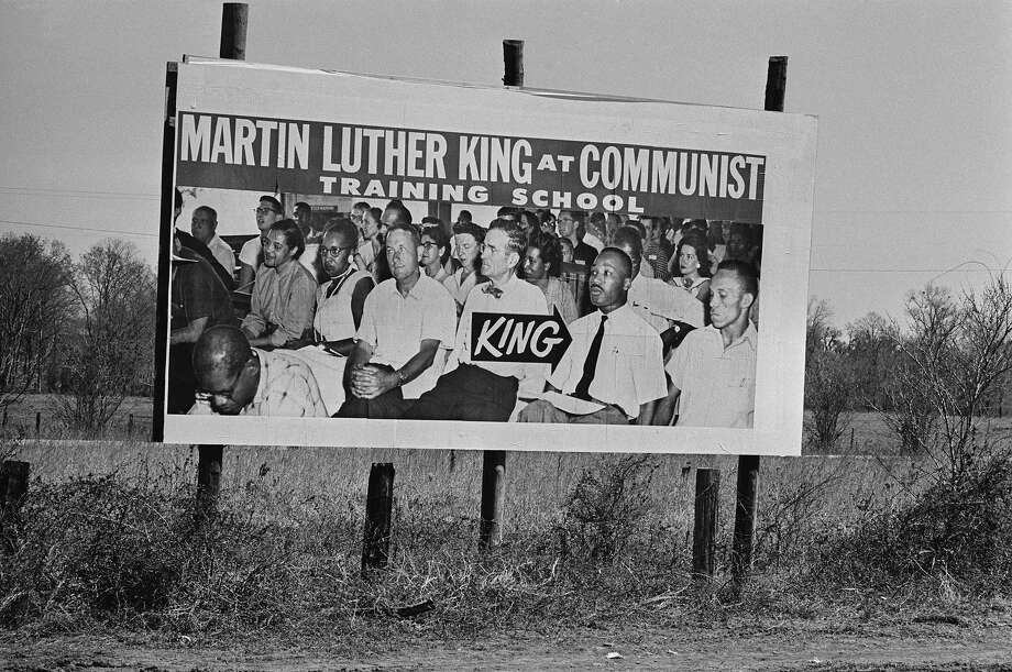 A large poster falsely purporting to show Dr. Martin Luther King, Jr. at a Communist Training School stands beside the route of the Alabama civil rights march which he led. Photo: William Lovelace, Getty Images / Hulton Archive