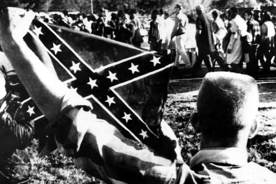 A white youth holds up a Confederate flag to antagonize civil rights marchers as they walk along the highway. Photo: Rolls Press/Popperfoto, Popperfoto/Getty Images / Popperfoto