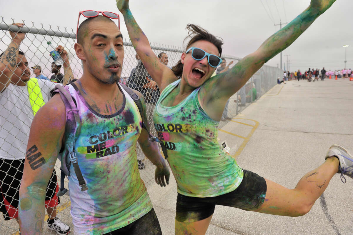 Covered in colored powder, David Pena and Melonie Mungia pose for a picture following the Color Me Rad 5K Run in the parking lot of the Freeman Coliseum.