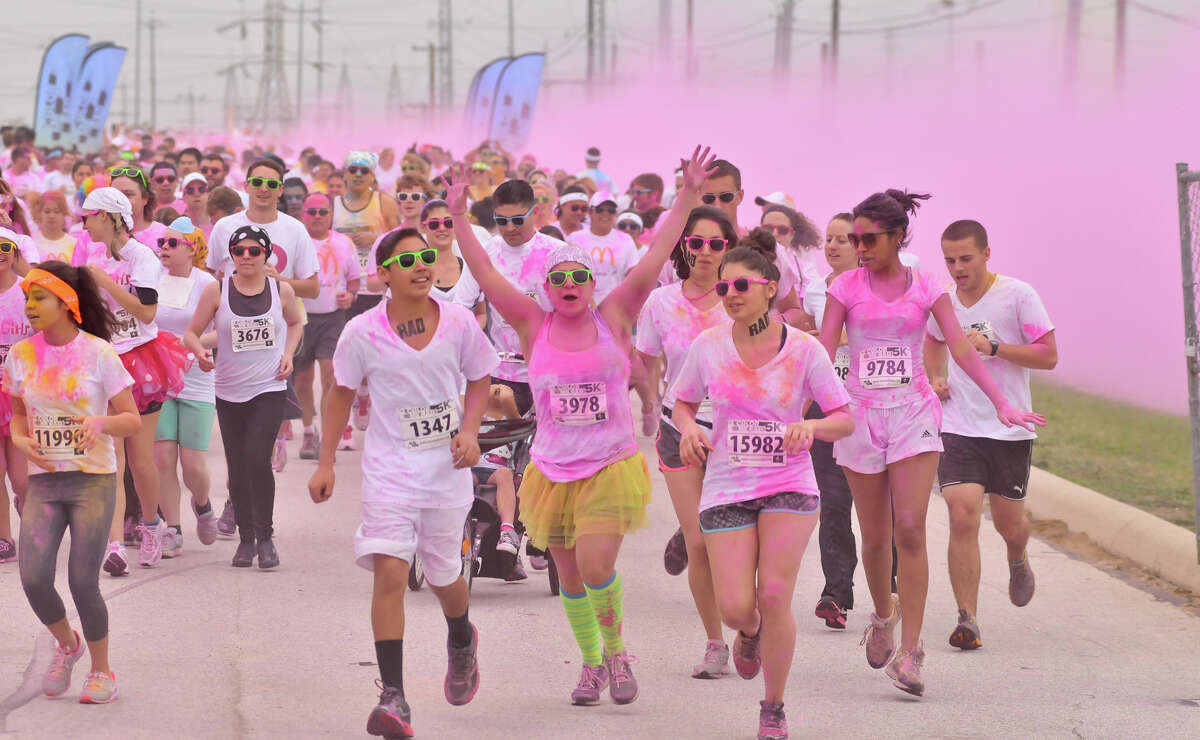 Runners get covered in pink powder during the Color Me Rad 5K Run in the parking lot of the Freeman Coliseum.