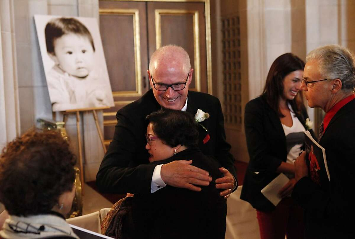 David Larson, Zheng Cao's husband, hugs Jaye Florendo, a family friend at the War Memorial Opera House following a memorial concert for Cao on Monday, June 24, 2013, in San Francisco, Calif. The Chinese-born mezzo soprano died this year after a long struggle with cancer.