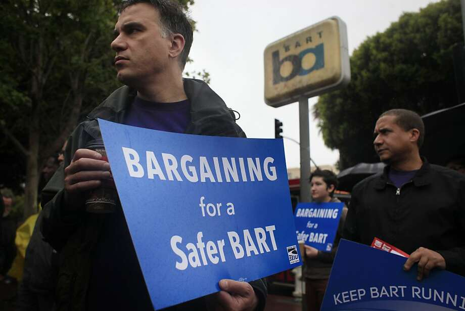 Ben Sizemore (left) and David Canham join other BART employees during a news conference and rally outside the 24th Street Station in San Francisco to show their support for a strike vote by unions. Photo: Mike Kepka, The Chronicle