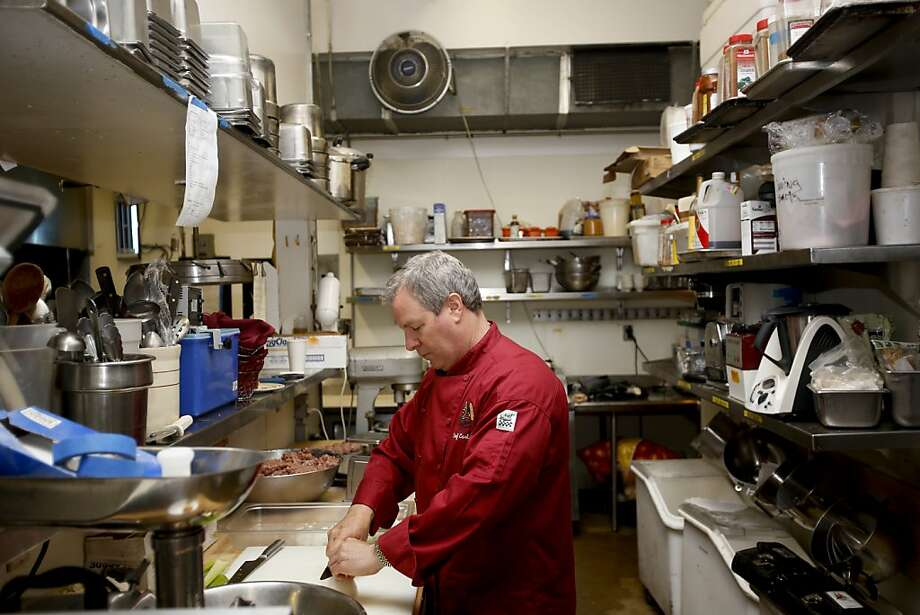 Chef-owner Alan Carlson chops onions at Italian Colors in Oakland, which is part of a class-action lawsuit over American Express credit card charges. It lost in a U.S. Supreme Court ruling on antitrust cases. Photo: Ian C. Bates, The Chronicle