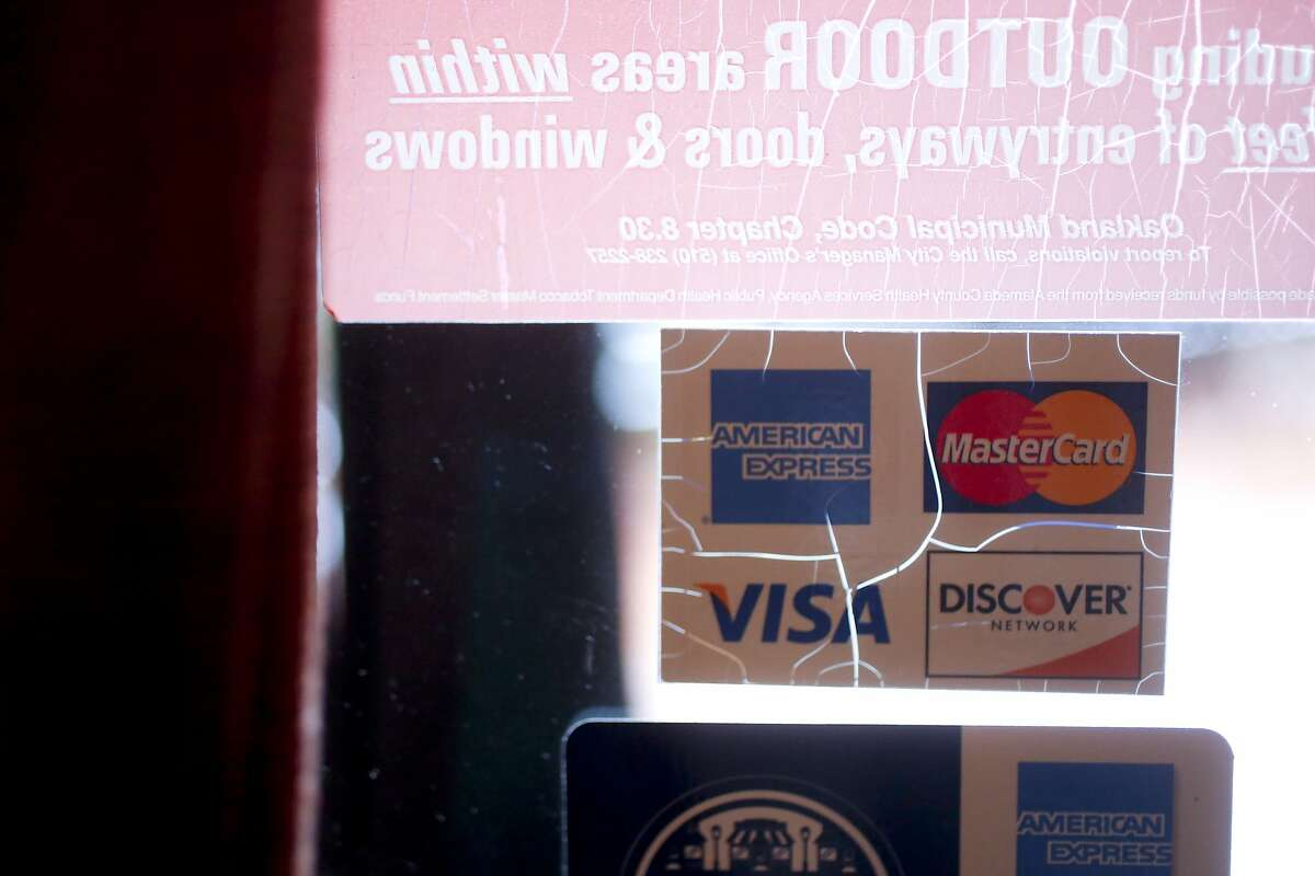 An accepted credit cards sign on the window of Italian Colors, a restaurant in Oakland's Montclair area, that is a part of a class action lawsuit against American Express in Oakland, Calif. on June 25, 2013.