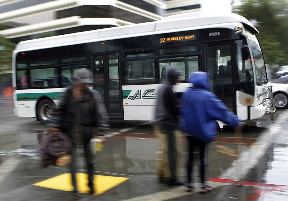 An AC Transit bus crosses 14th Street on Broadway in downtown Oakland, Calif. on Tuesday, June 25, 2013. Employees from both AC Transit could walk off the job Wednesday.