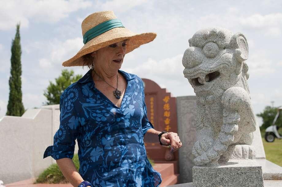 Barbara Hinton looks at a dog guarding Thanh Kim Tran's tomb at Hollywood Historic Cemetery. Photo: R. Clayton McKee, Freelance / ©2013 R. Clayton McKee