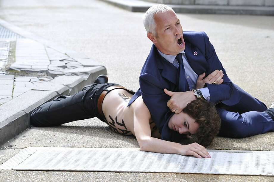 Topless vs. Tunisia:A security guard puts a Femen activist in a headlock after she and two half-naked companions tried to stop the car of the Tunisian prime minister from leaving the EU commission 
