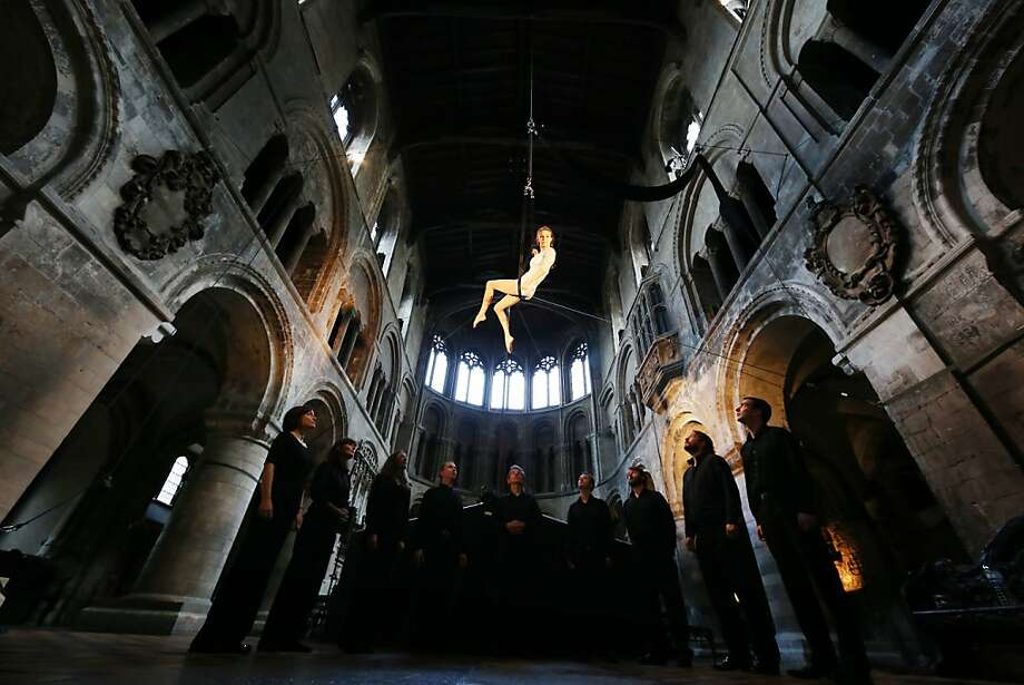 "Hitting the high notes: Bridie Hooper of Circa performs ""Stirrups"" while suspended above vocal ensemble I Fagiolini in St. Bartholomew the Great Church in London. The City of London Festival will be holding a variety of music, dance, art, film and poetry performances in some of the city's iconic spaces and venues. Photo: Peter Macdiarmid, Getty Images"