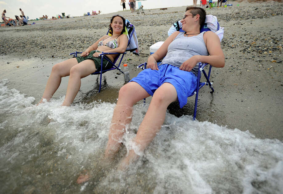 Kelly Dean, left, and Erin Garcia, both of Waterbury, keep cool with their feet in the surf at Silver Sands State Park in Milford on Monday, June 24, 2013. Photo: Brian A. Pounds / Connecticut Post