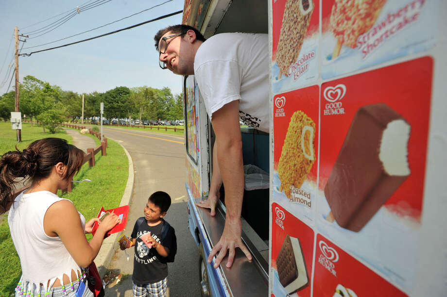 Ben Boger, owner of Ben's Ice Cream Truck, sells frozen treats to Odalys Leon, left, and her cousin Danny Cortezano outside Calf Pasture Beach in Norwalk on Tuesday, June 25, 2013. Photo: Jason Rearick / Stamford Advocate