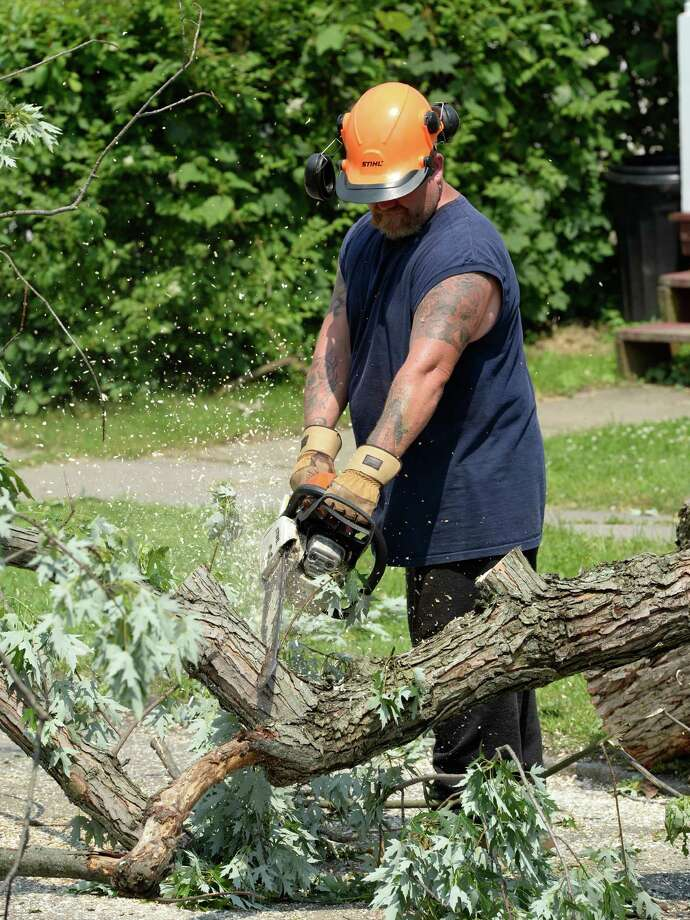 Jeff Cannon of KT Tree Service cuts down the limbs to be mulched as a massive tree is removed from the remains of a home at 1710 6th Street June 25, 2013 after a severe storm hit Rensselaer N.Y. last evening. KT Tree Service worked in the extreme heat to remove the remnants of the tree that destroyed the home where an elderly woman was brought to safety from the second floor after the storm.  (Skip Dickstein/Times Union) Photo: SKIP DICKSTEIN