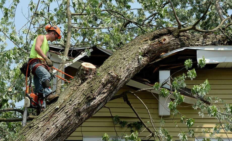 Kyle Trestizk of KT Tree Servce measures up one of the limbs of a massive tree which is being removed from the remains of a home at 1710 6th Street June 25, 2013 after a severe storm hit Rensselaer N.Y. last evening. KT Tree Service worked in the extreme heat to remove the remnants of the tree that destroyed the home where an elderly woman was brought to safety from the second floor after the storm.  (Skip Dickstein/Times Union) Photo: SKIP DICKSTEIN