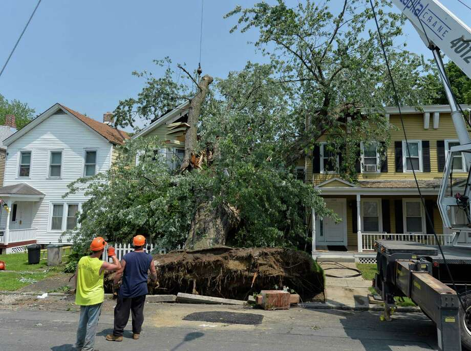 A massive tree is removed from the remains of a home at 1710 6th Street June 25, 2013 after a severe storm hit Rensselaer N.Y. last evening. KT Tree Service worked in the extreme heat to remove the remnants  of the tree that destroyed the home where an elderly woman was brought to safety from the second floor after the storm.  (Skip Dickstein/Times Union) Photo: SKIP DICKSTEIN
