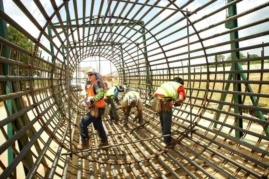 Construction crews build a form for a drill shaft that will be buried 95 feet into the ground to support a connector bridge during construction of the Grand Parkway near U.S. 290. Photo: Brett Coomer, Staff / © 2013 Houston Chronicle