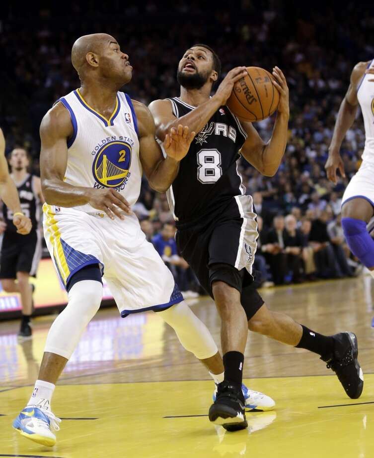 The Spurs' Patty Mills (8) dribbles to the basket as the Warriors' Jarrett Jack (2) defends in Oakland, Calif., on April 15, 2013.