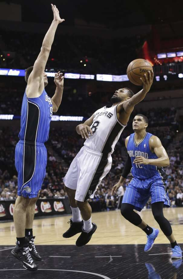 The Spurs' Patty Mills (8) tries an off-balance shot as the Magic's Nikola Vucevic (9) and Tobias Harris (12) defend pm April 3, 2013, in San Antonio.