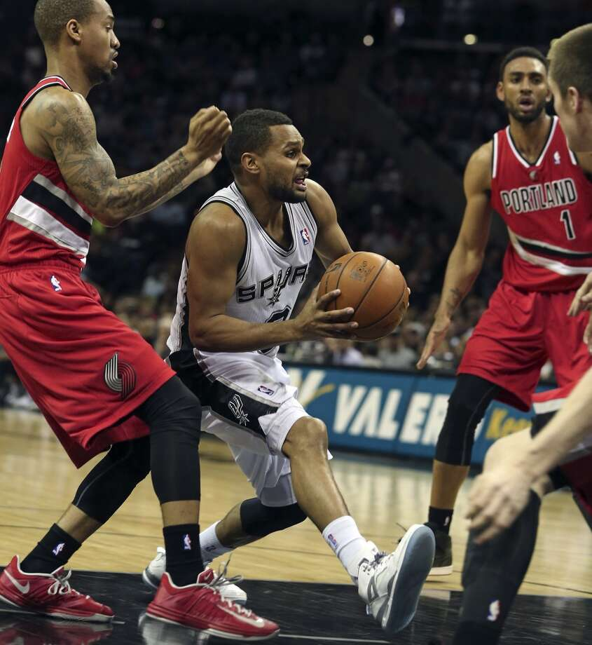 Patty Mills draws a crowd in the lane as the Spurs play the Trailblazers at the AT&T Center on March 8, 2013.