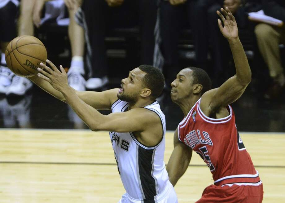 Patty Mills of the Spurs drives as Marquis Teague of the Bulls fouls him at the AT&T Center on March 6, 2013.