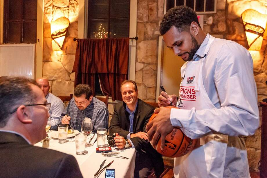 Spurs guard Patty Mills signs an autograph while waiting tables during the 2nd Annual Champions Against Hunger Dinner at the Grill in Leon Springs on Jan. 28, 2013.  The San Antonio Spurs players and coaches took a break from the court to don aprons as waiters and servers for the fundraising dinner benefitting the San Antonio Food Bank.