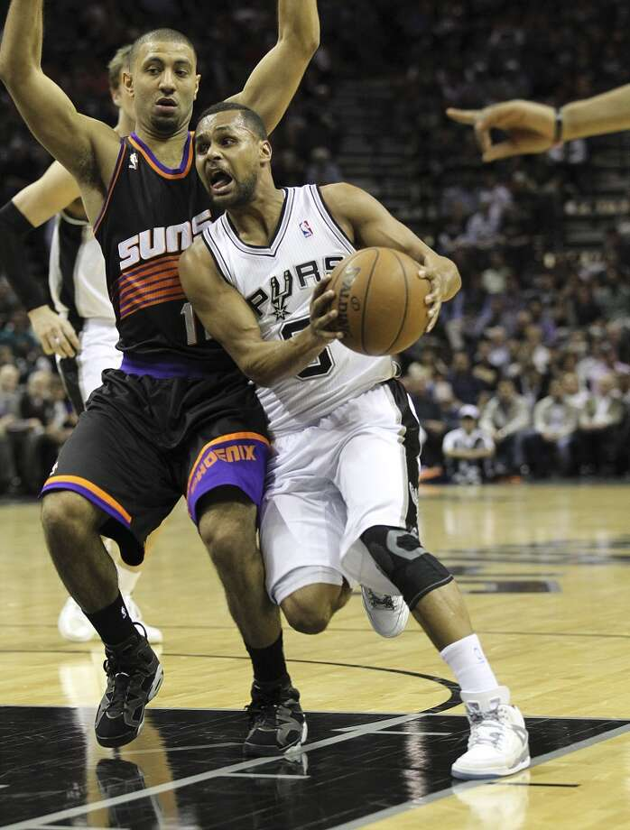 The Spurs' Patty Mills (8) drives the lane against the Suns' Kendall Marshall (12) at the AT&T Center on Feb. 27, 2013.