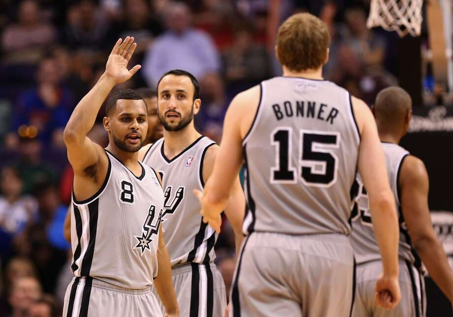 Patty Mills (8) of the Spurs high fives Matt Bonner (15) after scoring against the Phoenix Suns on Feb. 24, 2013 in Phoenix,.  The Spurs defeated the Suns 97-87.