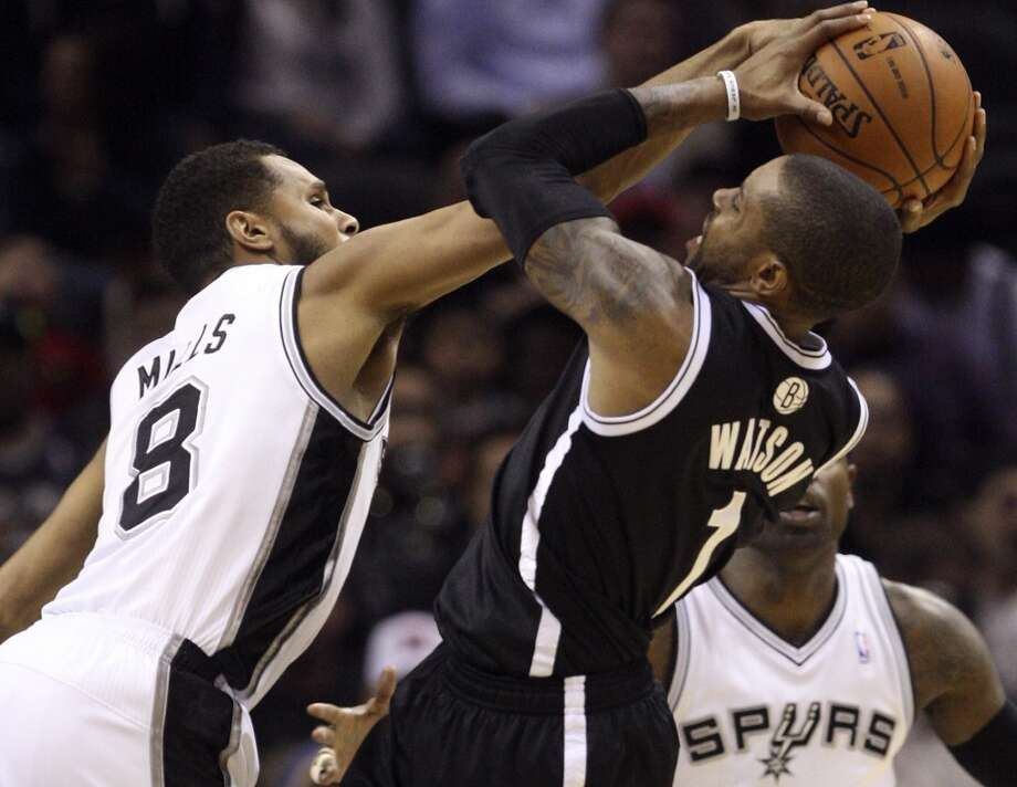 The Spurs' Patty Mills stuffs a shot by the Nets' C.J. Watson at the AT&T Center on Dec. 31, 2012. The Spurs won 104-73.