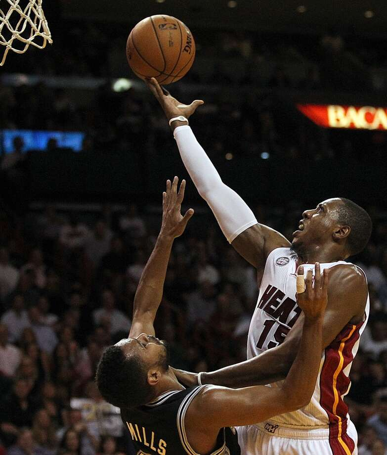 The Heat's Mario Chalmers shoots over the Spurs'  Patty Mills in Miami on Nov. 29, 2012.