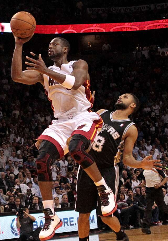 The Heat's Dwyane Wade  shoots to the basket chased by the Spurs' Patty Mills in Miami on Nov. 29, 2012.