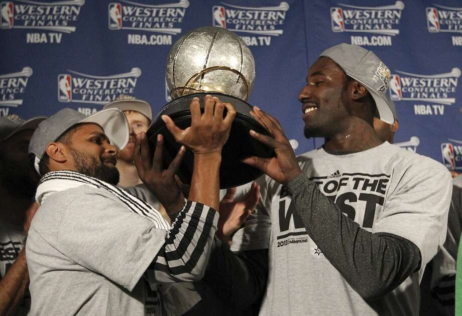 The Spurs' Patty Mills (left) and DeJuan Blair hold the 2013 Western Conference Championship trophy after the Spurs defeated the Grizzlies in four games to move to the NBA Finals on May 27, 2013.
