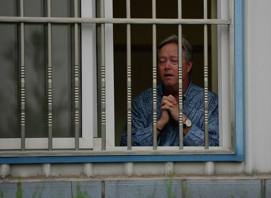 American Chip Starnes stands behind the bars of his office window after being held hostage in a wage dispute at his medical supply factory in Beijing. Photo: MARK RALSTON, Staff / AFP