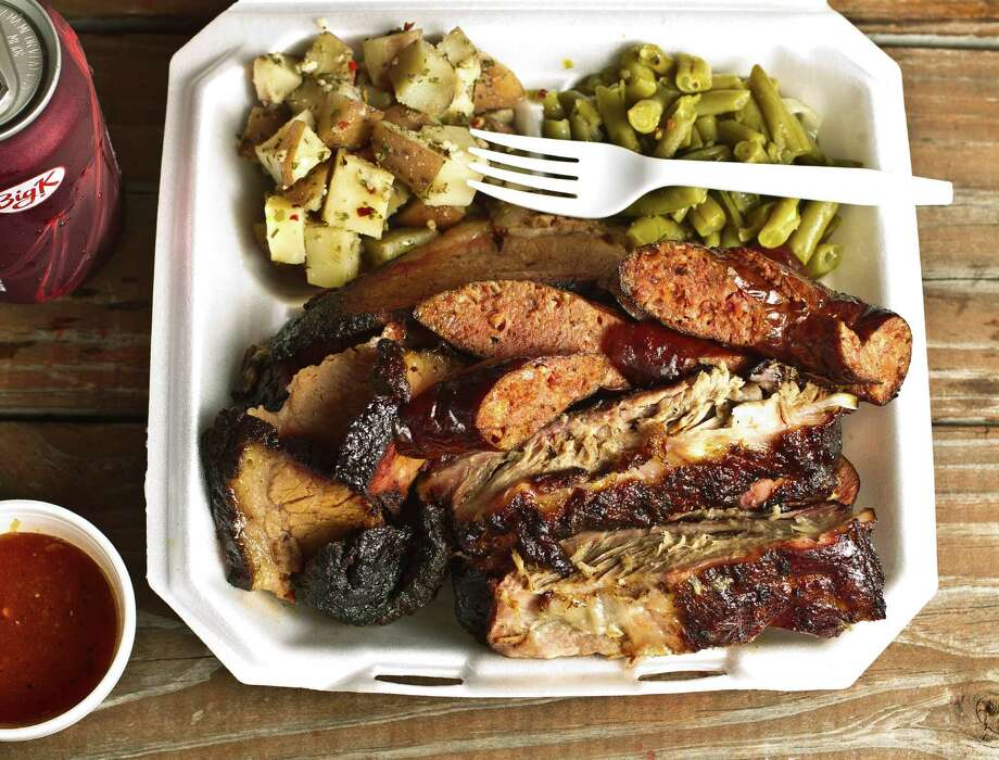 Brooks' Place BBQ's three-meat plate of sliced beef, pork ribs and sausage link is a marvelous thing. Photo: Nick De La Torre, Staff / © 2013  Houston Chronicle